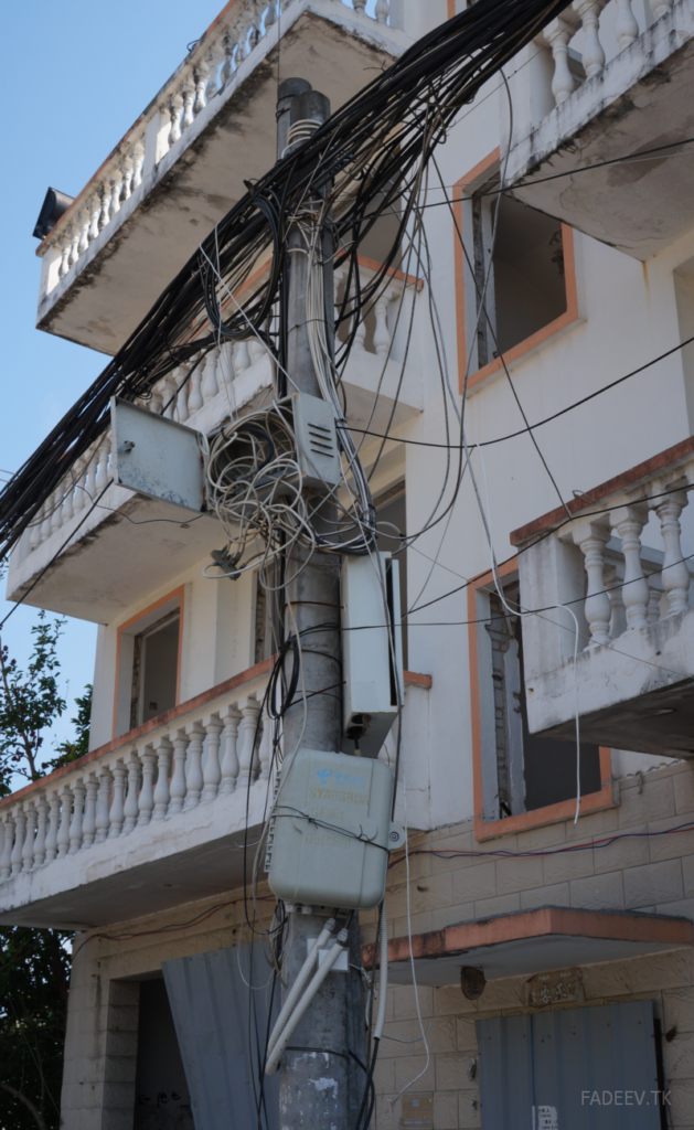 An utility pole in front of a demolition building in an old block. Sanya, Hainan Island, China