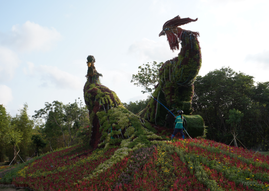 An employee irrigates a flower sculpture in a park in Sanya, Hainan Island, China